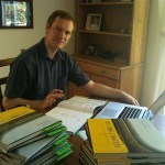 Photo of Andrew with his pile of books, signing them before sending them off. He's looking quite serious:-).