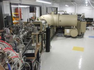 A tandem particle accelerator. A lab with a lot wiring and a tan, cylindrical accelerator.